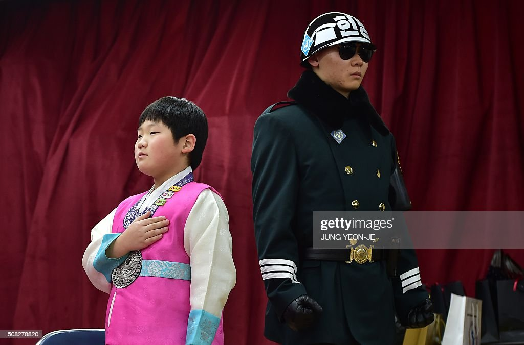 TOPSHOT - A graduate (L) wearing traditional dress salutes as a South Korean soldier (R) stands guard during a graduation ceremony for Taesungdong Elementary School at Taesungdong freedom village in the Demilitarized zone dividing the two Koreas in Paju on February 4, 2016. Six students graduated from the only school in this South Korean village sitting inside the demilitarized zone between North and South Korea.