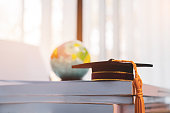 Graduated or Graduation university study abroad international Conceptual, Master cap on books stack with blur of america earth world globe model map in Library room of campus, Back to School