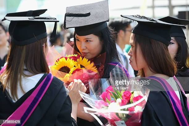 Graduates celebrate after leaving their graduation ceremony at the Royal Festival Hall on the Southbank in high temperatures on July 18 2013 in...