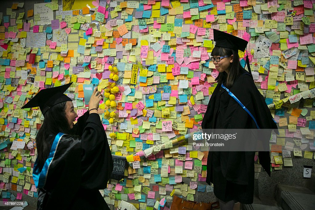 Graduates from the Hong Kong Polytechnic University pose for souvenir photos after their graduation ceremony at the main protest as a festival atmosphere prevails October 26, 2014 in Hong Kong, Hong Kong. A peaceful safe atmosphere remains at the massive protest site as artists freely express themselves and families bring their children to experience the Umbrella Revolution.
