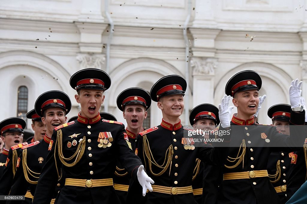 Graduates from the Suvorov military school throw coins into the air during a graduation ceremony at Sobornaya Square in Moscow's Kremlin on June 25, 2016. / AFP / VASILY