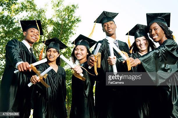 Jeunes diplômés tenant diplômes à l'extérieur