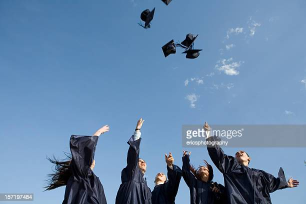 Graduates in gowns throwing mortar board caps into blue sky