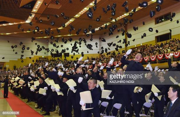 Graduates of the National Defense Academy of Japan toss their caps in the air during their graduation ceremony at its gymnasium in Yokosuka Kanagawa...