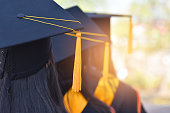 The back image of the graduates wearing a yellow tassel hat.