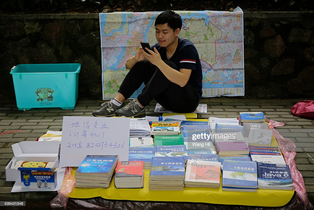 Graduates play mobile phone waiting for customers.College graduates sell their used textbooks, magazines, CD and other possessions on the campus of a university on May 29, 2016 in Wuhan, China. Graduates sell those things which are useless to them or are difficult to take them back home. on May 29, 2016 in Wuhan, China.