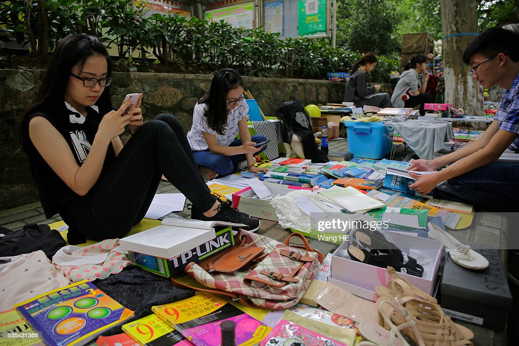 Graduates play phone waiting for customers. College graduates sell their used textbooks, magazines, CD and other possessions on the campus of a university on May 29, 2016 in Wuhan, China. Graduates sell those things which are useless to them or are difficult to take them back home. on May 29, 2016 in Wuhan, China.
