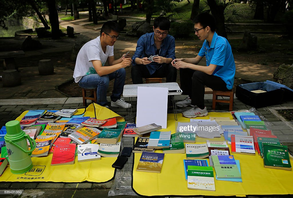 Graduates play poker to wait for customers.College graduates sell their used textbooks, magazines, CD and other possessions on the campus of a university on May 29, 2016 in Wuhan, China. Graduates sell those things which are useless to them or are difficult to take them back home.on May 29, 2016 in Wuhan, China.