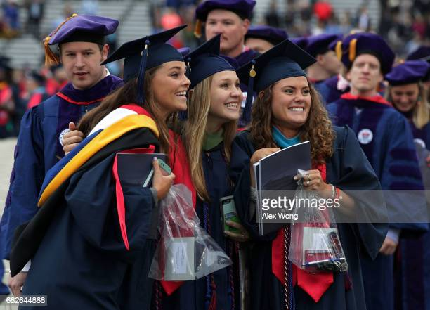 Graduates pose for photos as they enter the football field prior to the commencement at Liberty University May 13 2017 in Lynchburg Virginia...