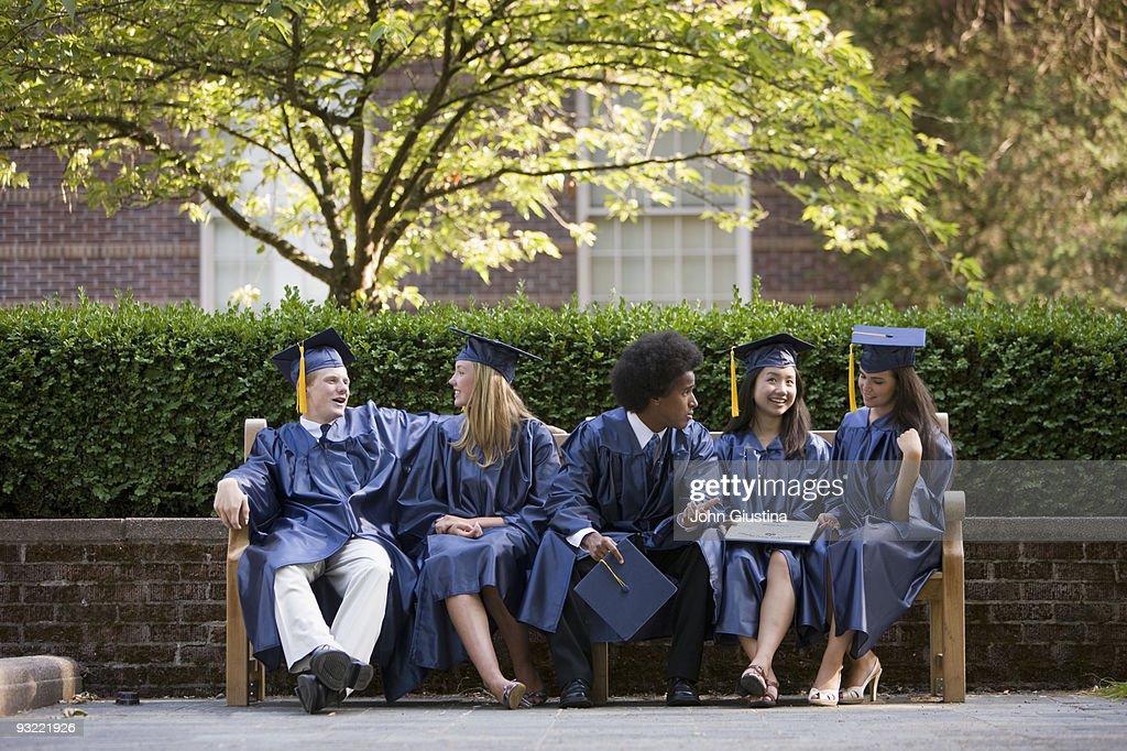 Graduates relax and talk after graduation. : Stock Photo