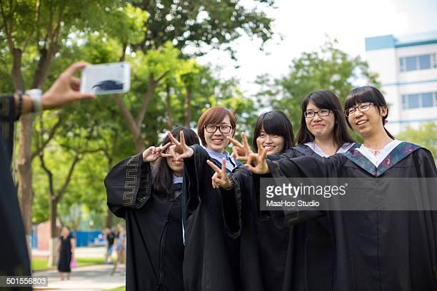 Graduates taking portrait together outdoors