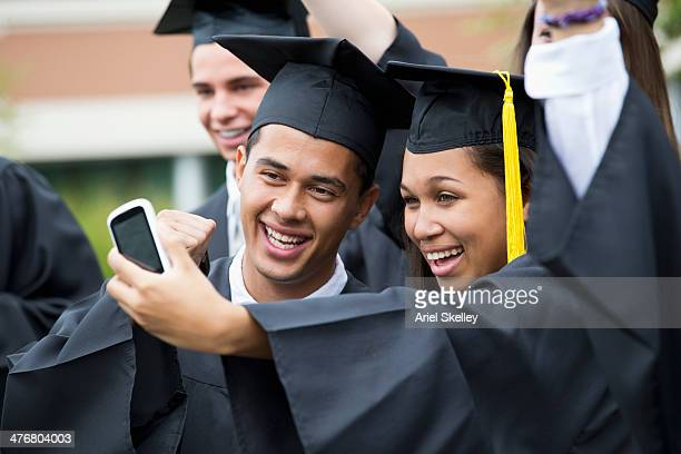Graduates taking self-portrait together outdoors