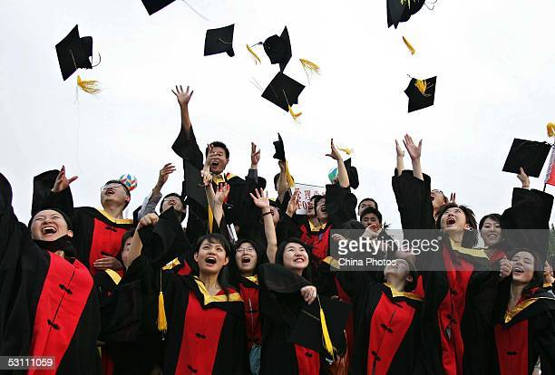 Graduates throw their caps during the graduation ceremony at Shanghai Jiaotong University on June 20 2005 in Shanghai China According to the Ministry...