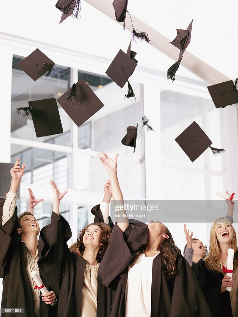 Graduates throwing mortarboards in air : Stock Photo
