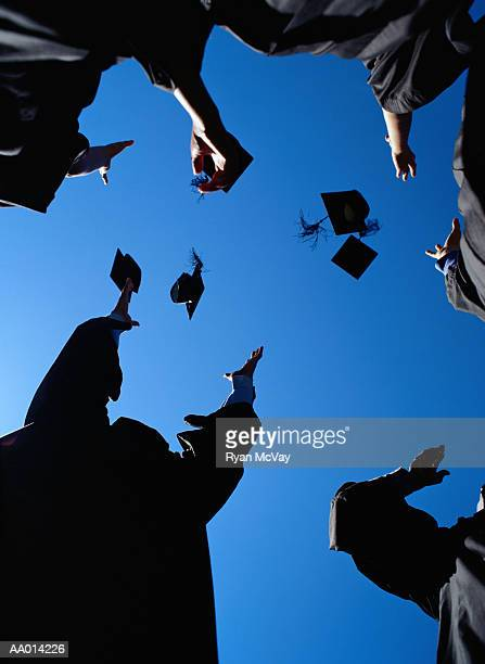 Graduates throwing mortarboards in the air, low angle view