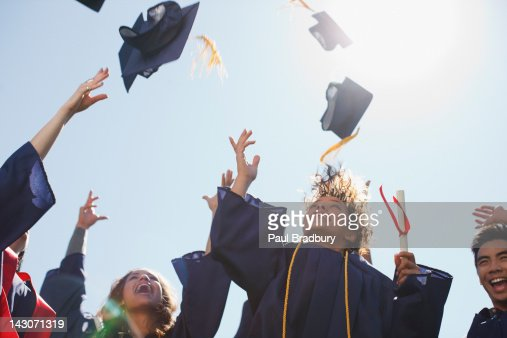 Graduates tossing caps into the air : Stock Photo