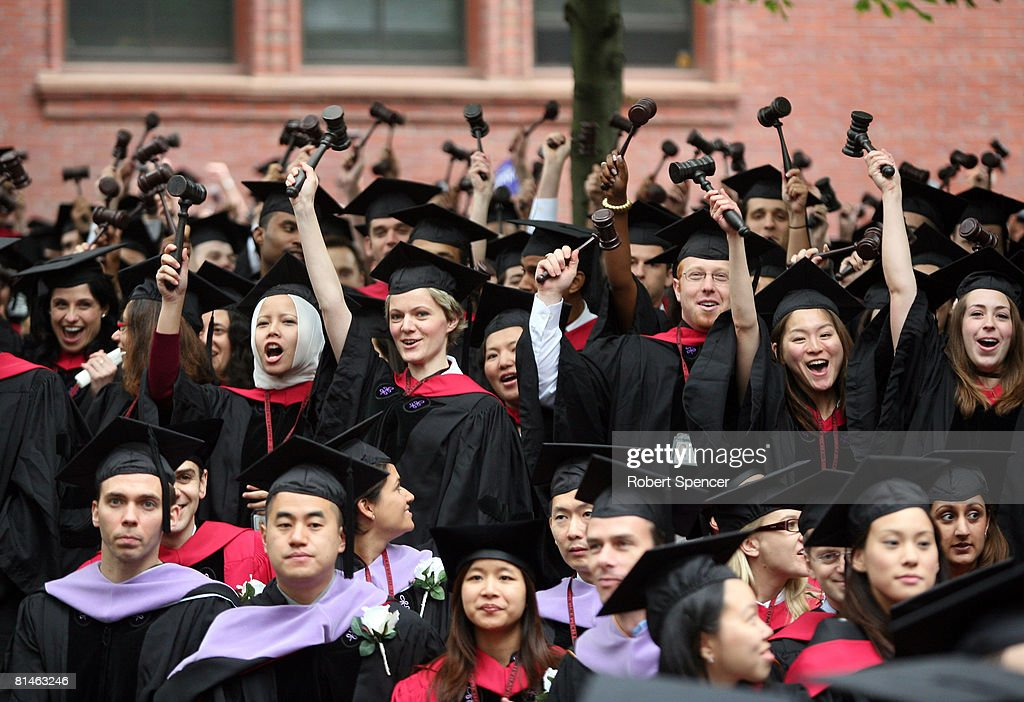 Graduating Harvard University Law School students stand and wave gavels in celebration at commencement ceremonies June 5 in Cambridge Massachusetts...