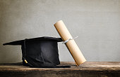 graduation cap, hat with degree paper on wood table Empty ready for your product display or montage.