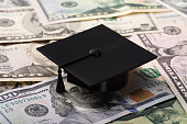 Close-up Of Black Graduation Cap On Dollar Banknotes