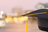 graduation cap with gold tassel on Abstract bokeh blur background.'n