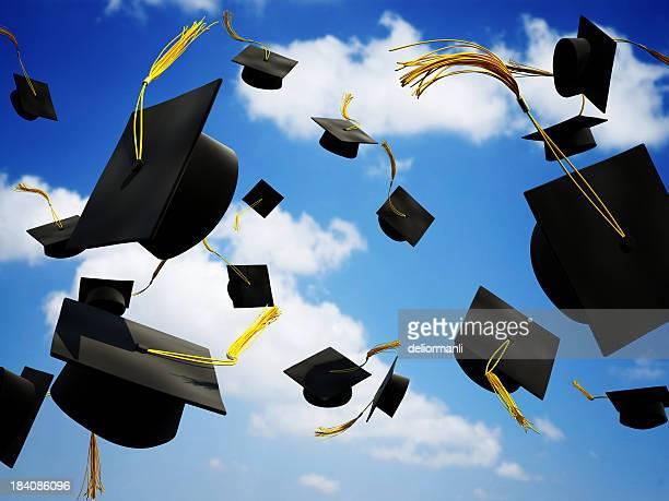 Graduation caps in die Luft geworfen