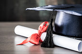 Graduation hat and diploma on table