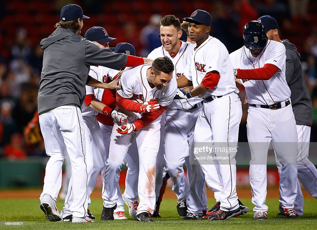 Grady Sizemore of the Boston Red Sox is mobbed by teammates including Will Middlebrooks and Jonathan Herrera ##10 after hitting his walkoff hit in...