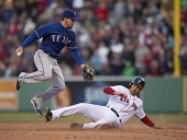 Grady Sizemore of the Boston Red Sox slides into second to break up a double play attempt by Donnie Murphy of the Texas Rangers in the ninth inning...