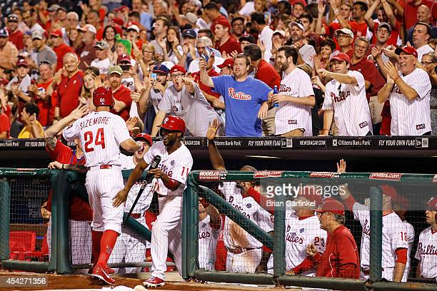 Grady Sizemore of the Philadelphia Phillies is congratulated by teammates in the dugout after hitting a two run home run in the sixth inning of the...