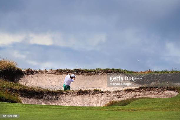 Graeme McDowell of Ireland chips out of a bunker during day three of the World Cup of Golf at Royal Melbourne Golf Course on November 23 2013 in...
