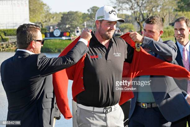 Graeme McDowell of Northern Ireland and Sam Saunders present Marc Leishman of Australia with Arnold Palmer's red cardigan after he won the Arnold...