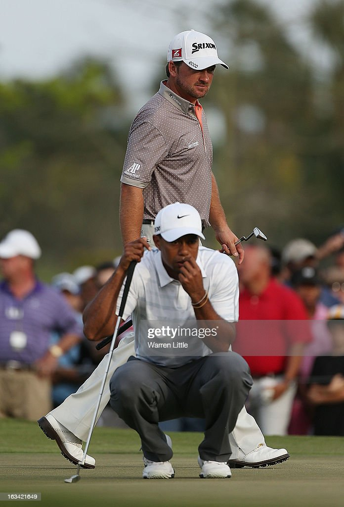 Graeme McDowell of Northern Ireland and Tiger Woods wait on the 15th green during the third round of the World Golf Championships-Cadillac Championship at the Trump Doral Golf Resort & Spa on March 9, 2013 in Doral, Florida.