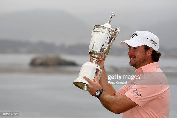 Graeme McDowell of Northern Ireland celebrates with the trophy on the 18th green after winning the 110th US Open at Pebble Beach Golf Links on June...