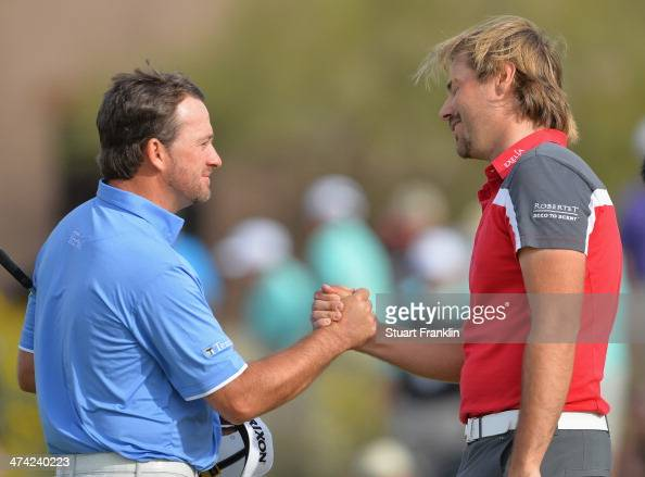 Graeme McDowell of Northern Ireland congratulates Victor Dubuisson of France on the 18th hole during the quarterfinal round of the World Golf...