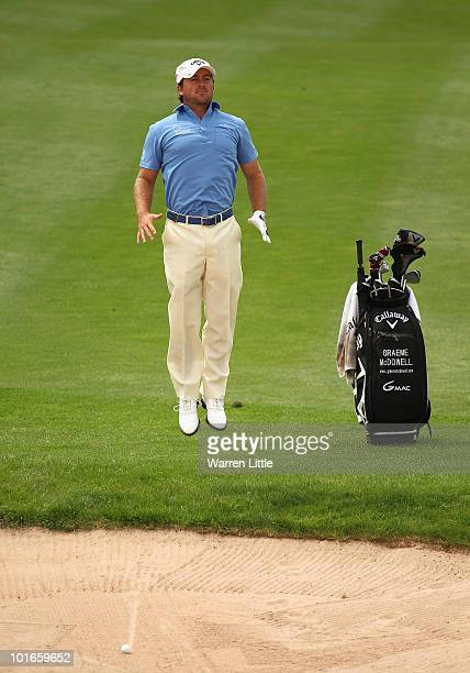 Graeme McDowell of Northern Ireland jumps to see the line of his shot out of the fairway bunker on the seond hole during the final round of the...