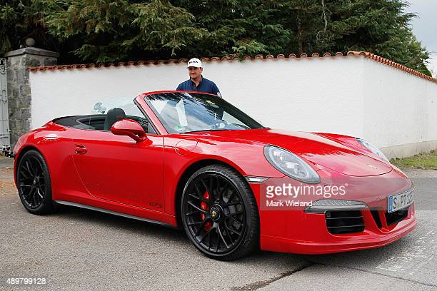 Graeme McDowell of Northern Ireland takes a Porsche Carrera 911 4 GTS for a test drive after the first round of the Porsche European Open at Golf...