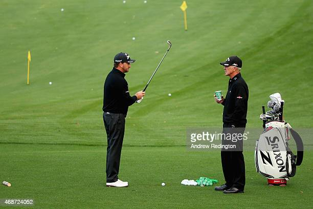 Graeme McDowell of Northern Ireland talks with his coach Pete Cowen on the range during a practice round prior to the start of the 2015 Masters...