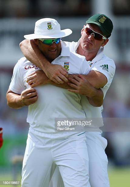 Graeme Smith of South Africa congratulates Jacques Kallis of South Africa after he caught out Alastair Cook of England for 7 runs off the bowling of...