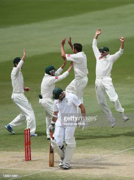 Graeme Smith of South Africa leaves the field after getting out as Australian players celebrate during day four of the Second Test Match between...