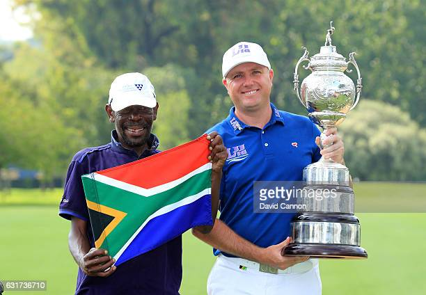 Graeme Storm of England poses with the trophy and his caddie Jeffrey Wkonyane after hi splayoff win in the final round of the 2017 BMW South African...