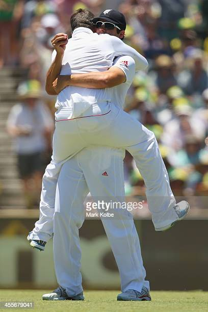 Graeme Swann of England and Alastair Cook of England celebrate after combining to take the wicket of Michael Clarke of Australia during day one of...