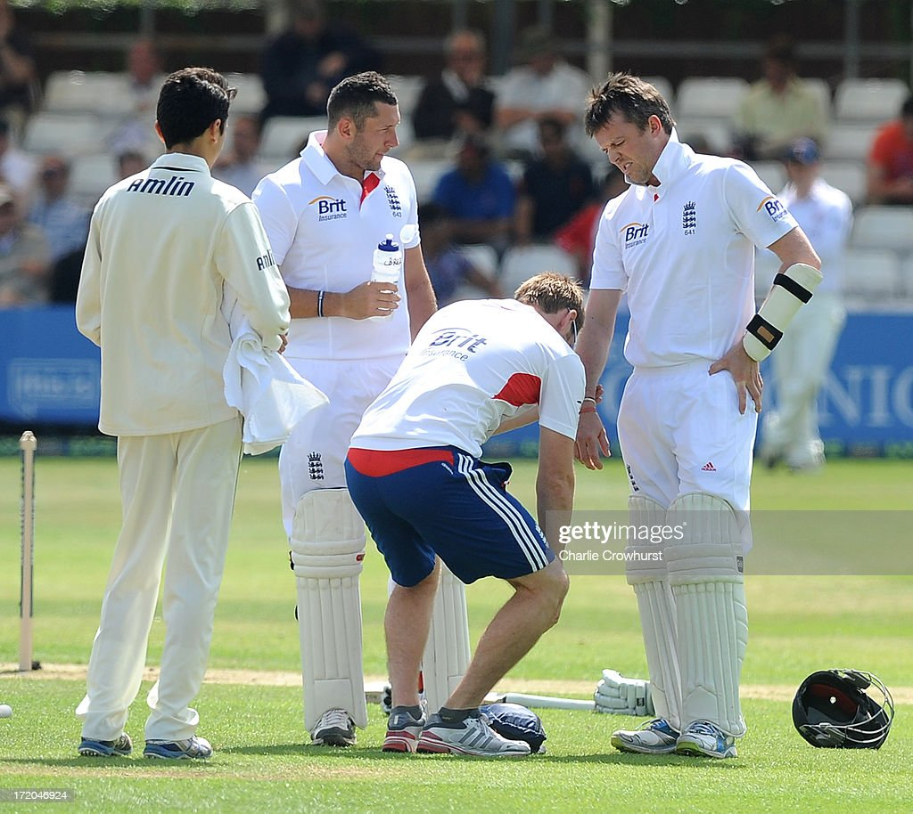 Graeme Swann of England gets medical attention on his forearm after being hit by a ball from Essex's Tymal Mills during the LV=Challenge Day 2 match between Essex and England at Ford County Ground on July 01, 2013 in Chelmsford, England.
