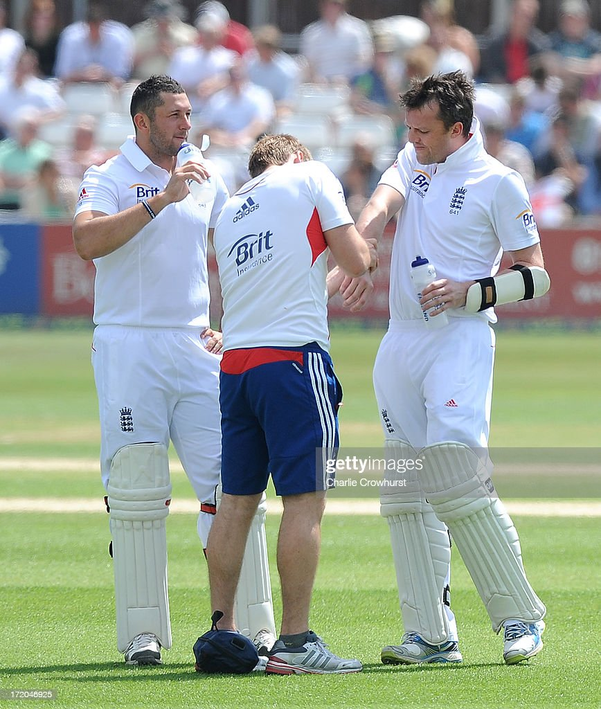 Graeme Swann of England gets medical attention on his forearm after being hit by a ball from Essex's Tymal Mills during day three of the LV=Challenge Day 2 match between Essex and England at Ford County Ground on July 01, 2013 in Chelmsford, England.