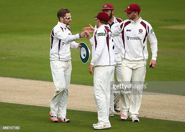 Graeme White of Northamptonshire celebrates with teammates after taking the final Surrey wicket of Matt Dunn on day three of the LV County...