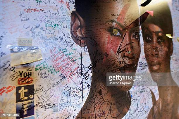 Graffiti and other writings cover a nearby commercial billboard two weeks after the death of Brixton born English singer songwriter David Bowie at...