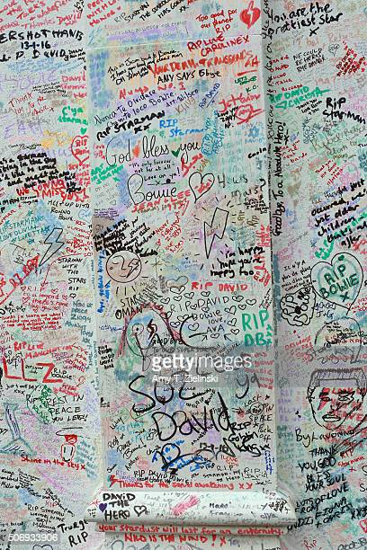 Graffiti and other writings cover a wall to the left side of the flowers and other items left on a mound that continues to grow two weeks after the...