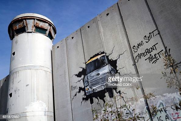 TOPSHOT Graffiti and slogans are seen on the Israel's controversial separation barrier between the West Bank city of Bethlehem and Jerusalem on...
