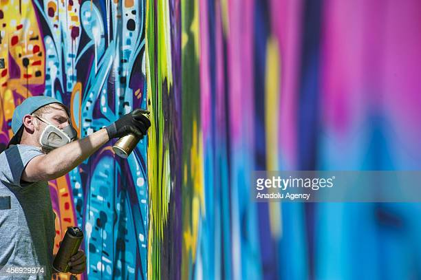 A graffiti artist at work is seen during the 4th annual City Of Gold Urban Art Festival in Johannesburg South Africa on October 9 2014 The aim of...