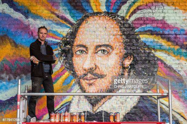 Graffiti artist James Cochran aka Jimmy C poses for a photograph beside his mural of William Shakespeare on Clink Street near the Shakespeare's Globe...