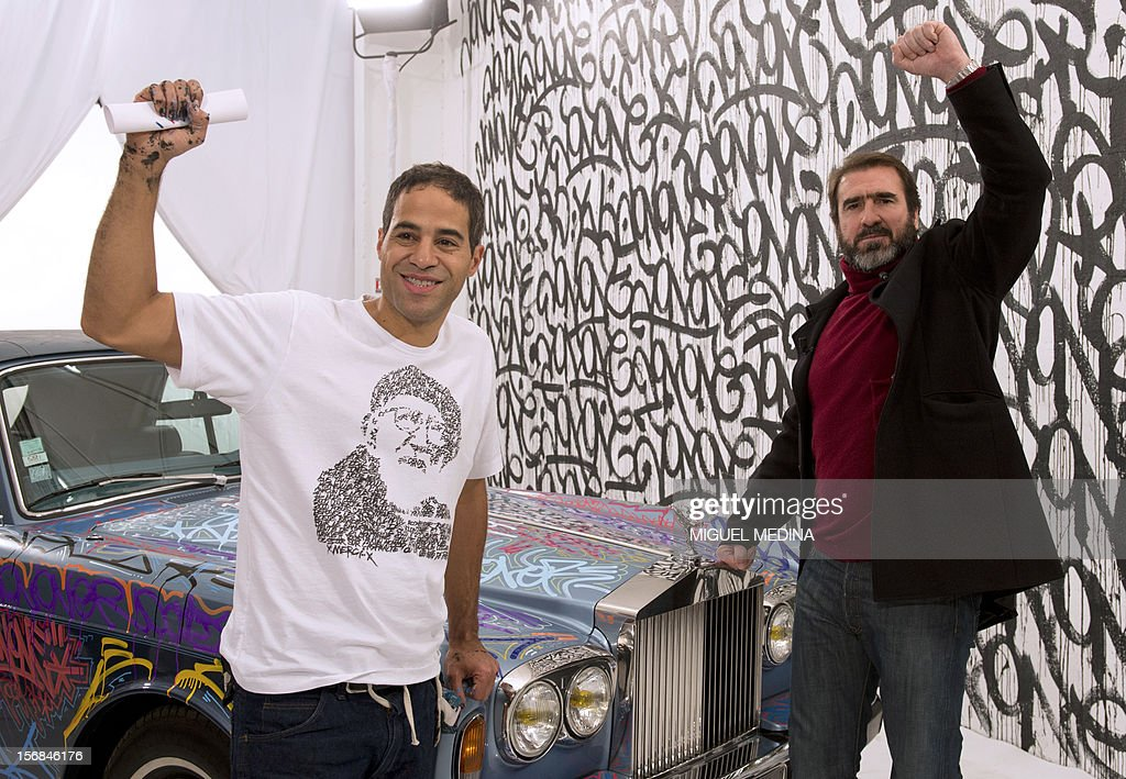 US graffiti artist Jonone and former football player turned actor Eric Cantona pose next to a Rolls Royce during the TV show 'Le grand journal' on a set of French TV Canal+, on November 22, 2012 in Paris during the launching of French charity association Abbe Pierre Foundation's winter campaign. AFP PHOTO / MIGUEL MEDINA